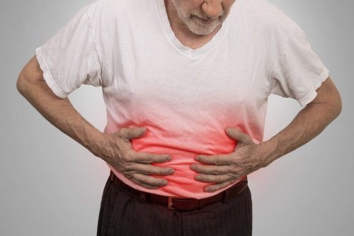 Stomach ache, man placing hands on the abdomen isolated on gray wall background